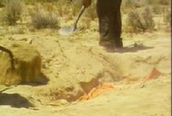 Leon using a shovel to dig s a hole in the new mexico desert