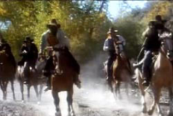 A gang of men with cowboy hats and bandanas around their faces riding horses