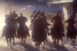 A posse of cowboys riding horses with guns