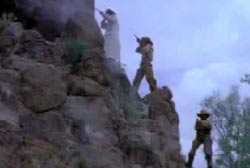 Three gunmen on the side of a ridge shoot at smugglers with rifles