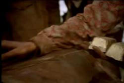 a man taking gold bars out from a chest