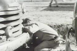 Doc Noss slumped over on the bumper of his car