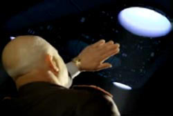 A man using his hand to shield the light emanating from the UFO