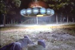 Two airmen laying on the ground, looking up at a hovering saucer with many lights