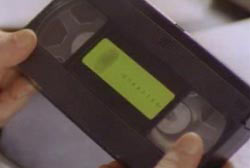 A person holding a VHS tape