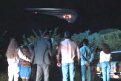 A large group of onlookers staring at a UFO in the night sky