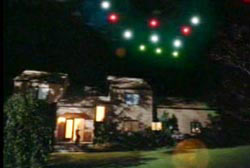 Many lights in varying colors arranged in the sky in a tight formation over a suburban home