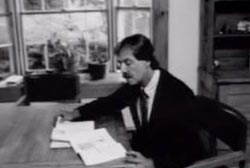 Dennis Sant in a suit and tie sitting at a table reading through two books