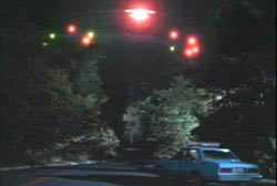 A police cruiser stopped in the middle of a road facing an unidentified flying object in the sky
