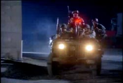 4 fully armed military personel riding in an olive jeep