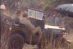 Two military personel riding a jeep in the desert towards a crashed unidentified craft