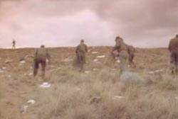 Military presonel holding bags, picking up the debris scattered in the desert