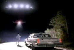 Betty Cash standing next to her car on a deserted road looking up at a flying disk in the sky with many lights (UFO)