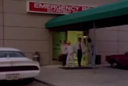 Betty being escorted out of an emergency room by a doctor and nurse