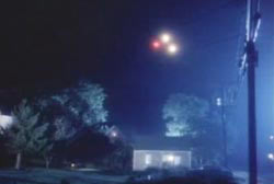 Three lights in the night sky in a tight formation. One light is red while the two other lights are yellow