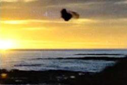 A strange dark object in the sky over the ocean