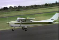 A Cessna 182 airplane lifting off from a landing strip