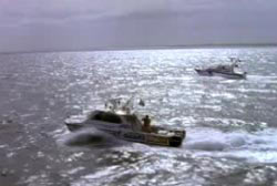 Two search boats driving slowly through the ocean