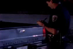 police officer wirting a ticket for Andre in a pickup truck