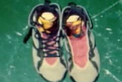 A pair of shoes on the floor. One shoe is missing its shoelace
