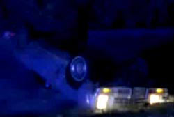 An overturned car in the middle of night with its headlights on