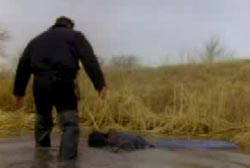 A police investigator wading through mud to reach the remains of their victims