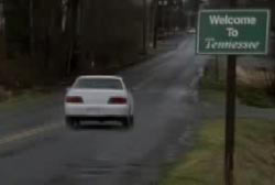 Blair driving a white car down a road with a sign tha reads 'Welcome to Tennessee