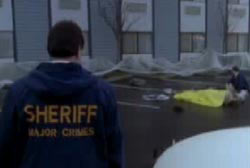 Police sheriff walking up to the scene of the crime where an officer is covering Blair's body