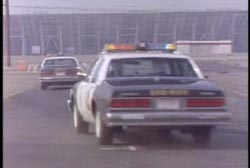 Two police cruisers driving down a highway