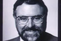 Smiling Chuck Morgan with glasses and suit