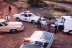 Police officers and paramedics wheeling away the covered body Chuck Morgan on a stretcher