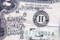 A $2 bill with various alphabetic markings scribbled on it