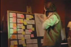 Dan writing on a chalk board filled with post it notes while he talks on a landline phone