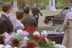 Funeral goers watching a mysterious man walk away from the funeral