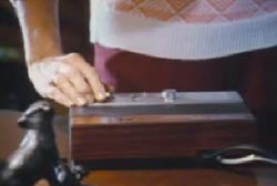 A woman standing over and turning the dial on the machine
