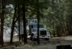 A white semi-truck driving through the woods