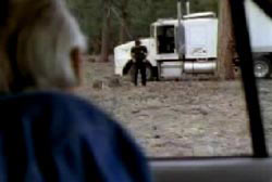 An older man watching the driver of the semi truck get out of his car