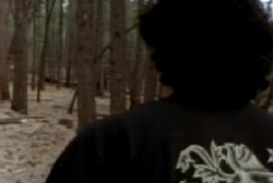 A man with curly black hair walking through the woods
