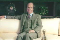 Ed Baker sitting on a white couch in a suit and tie
