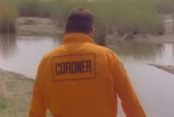 A coroner in an orange jumper walking up to a swampy body of water
