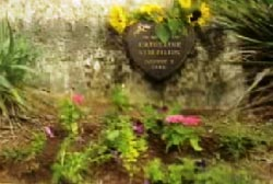 A plaque surrounded by foliage and flowers commemorating the life of Katherine