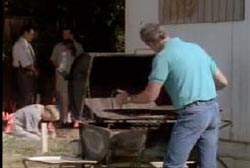 Man opening a barbeque that is filled with bones