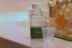 A bottle of medicine on a bathroom countertop thats filled with green liquid