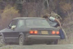 A hitchhiker talking to Philip through the open passenger side window