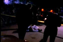 Police investigators surrounding the dead body of Ted in the middle of a street with yellow tape around the scene