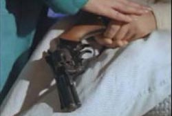A revolver resting in Tommy's hands