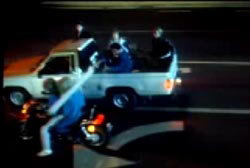 While driving parallel to each other a man in the bed of a pickup truck strikes the head of a woman on the back of a motorcycle