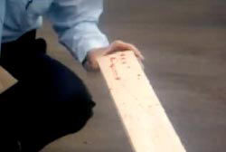Investigator examining a bloodied 2x4