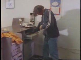 Suspect taking cash out of the post office cash register