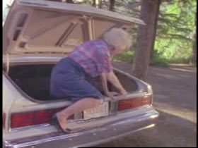 Opal climbing out of the trunk of the car